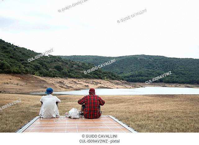 Rear view of young men sitting on wooden pier looking at mountain range, Nuoro, Sardinia, Italy