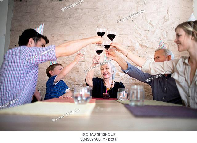 Family toasting with red wine at dinner table