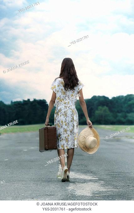 a woman in a floral dress is walking away