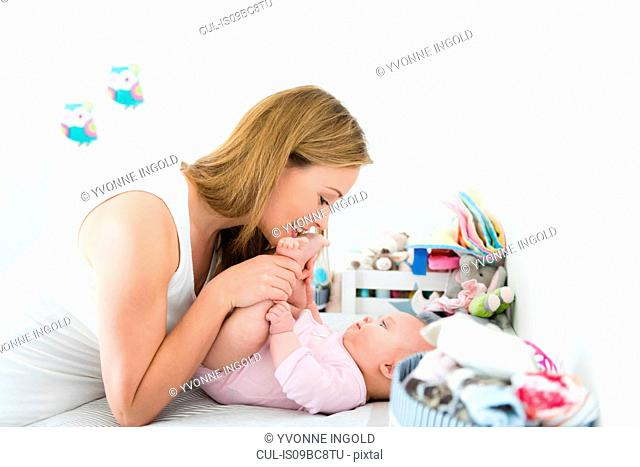 Mother playing with baby on changing table