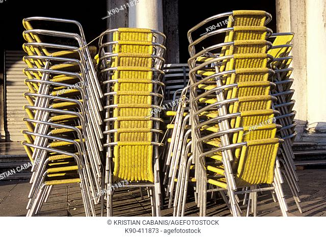 Pile of yellow chairs outside of a restaurant at Piazza San Marco, Venice, Italy, Europe