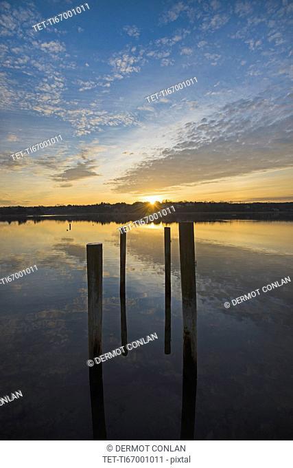 USA, Massachusetts, Cape Cod, Eastham, Mooring posts in lake at sunrise