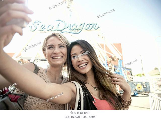 Two women at fairground, taking self portrait with smart phone
