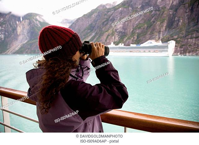 Woman using binoculars on cruise ship, Ketchikan, Alaska, USA