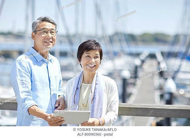 Japanese senior couple having fun by the sea