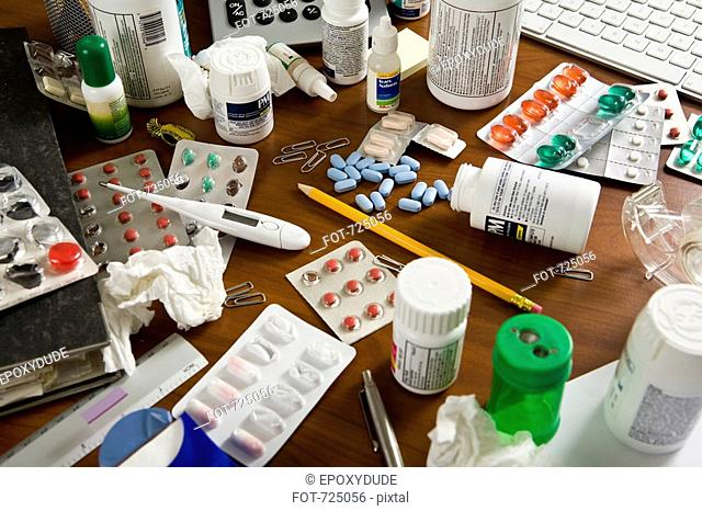 An office desk cluttered with various medicines