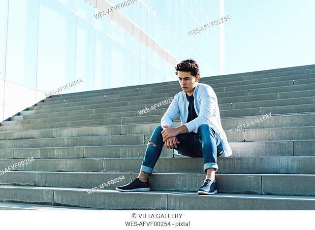 Serious young man sitting on stairs outdoors