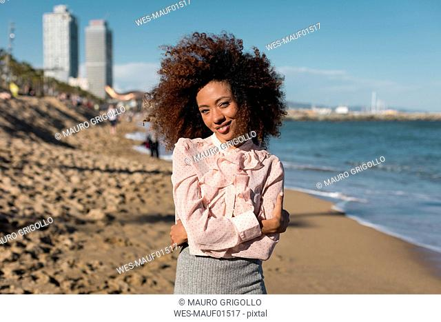 Portrait of smiling beautiful young woman with afro hairdo standing on the beach