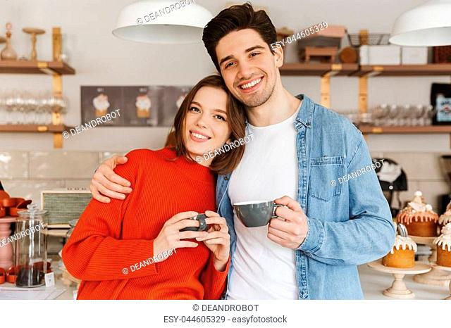 Beautiful couple woman and man in casual wear smiling and standing with cups of coffee in cozy cafe