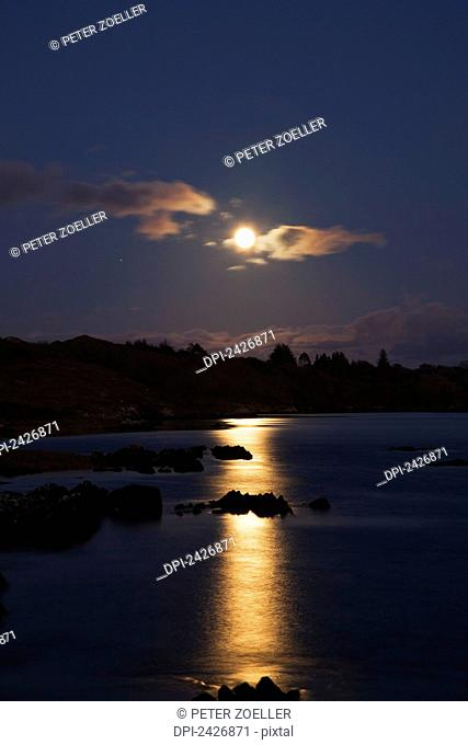 Moonrise reflected in tranquil water; Tahilla, County Kerry, Ireland