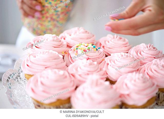 Woman decorating cupcakes with sugar sprinkles