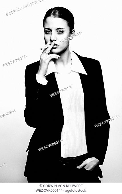 Young woman in suit smoking