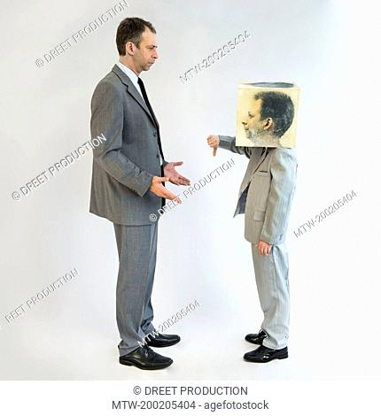 Boy wearing mask and showing thumbs down to businessman