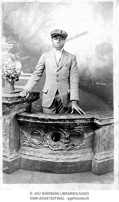 Three quarter length standing portrait of young African American man, wearing dark suit, light shirt and hat, standing at counter in front of backdrop