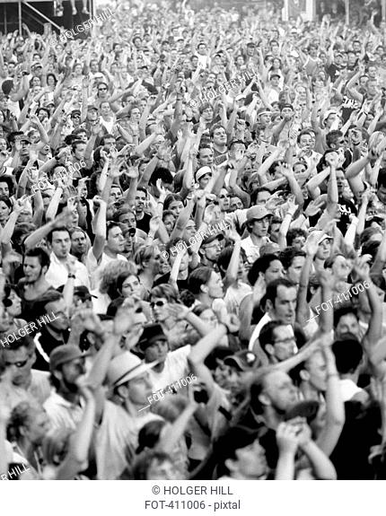 Large crowd of people with their arms raised