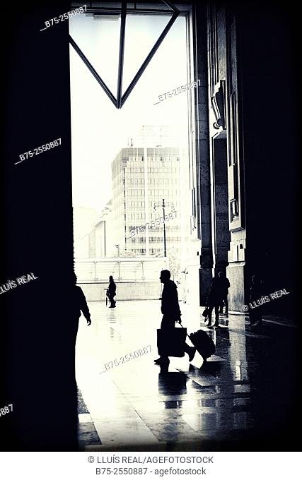 Unrecognizable silhouette of a man walking with a suitcase outside the Milan train station, Italy, Europe