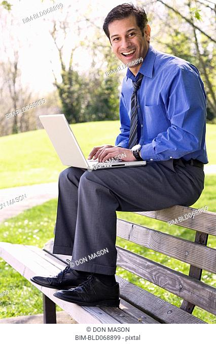 Hispanic businessman using laptop outdoors