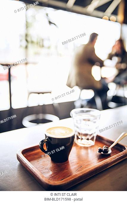 Tray of coffee, coffee beans and water in cafe