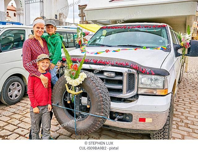 Portrait of mother and sons beside recreational vehicle, Copacabana, Oruro, Bolivia, South America