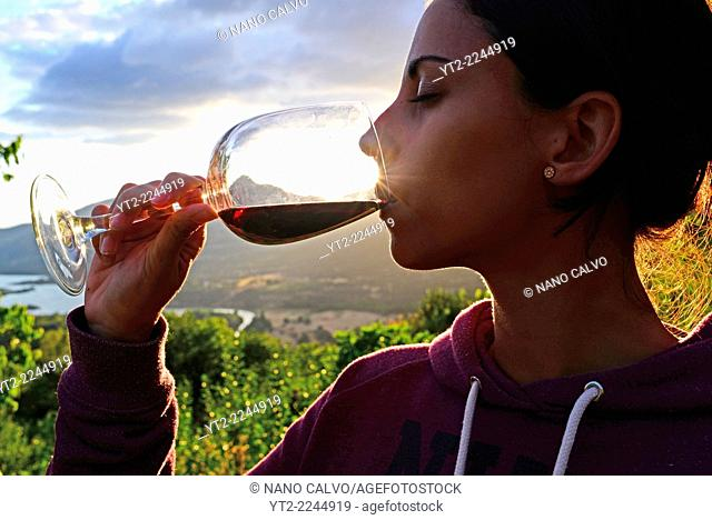 Young woman drinks wine at sunset in valley