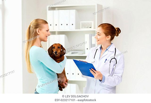medicine, pet care and people concept - happy woman holding dachshund dog and veterinarian doctor with clipboard at vet clinic