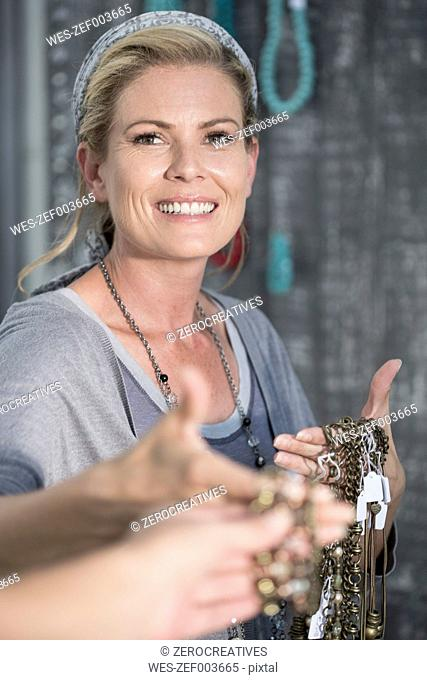 Smiling woman showing necklaces to a customer