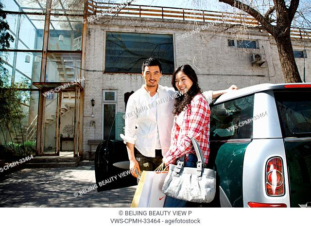 A woman and man standing by a car in front of studio