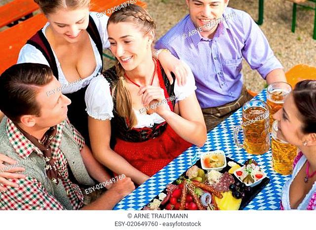 Im Biergarten - Freunde am Biertisch in Tracht