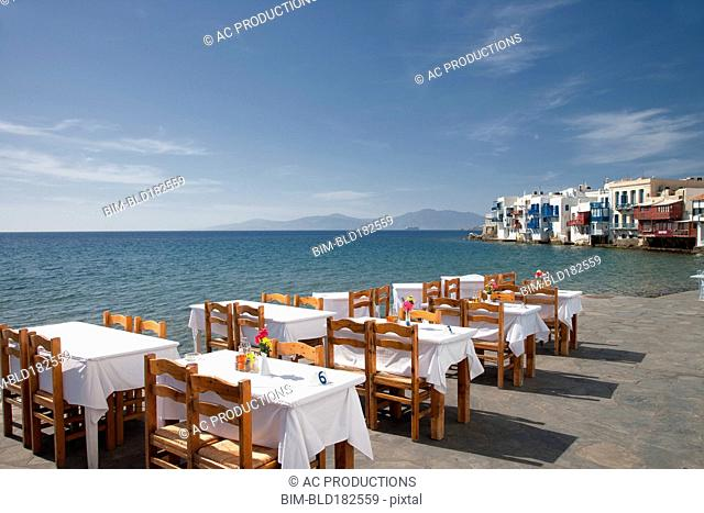 Tables at waterfront cafe under blue sky