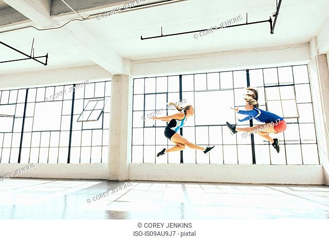 Low angle side view of young women in gym doing mid air lunge