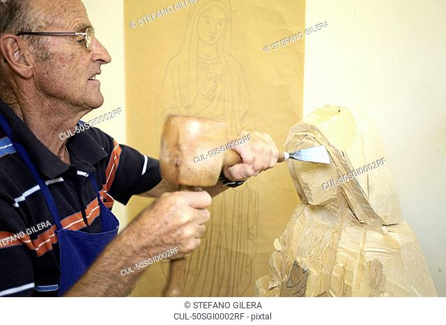 Sculptor chiseling figure from wood