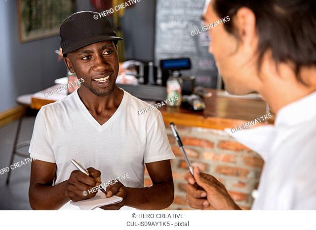 Employee in restaurant talking with chef, making notes in notebook