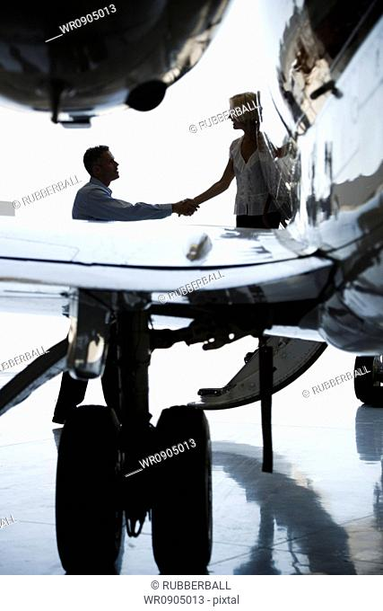Businessman shaking hands with a businesswoman stepping down from an airplane