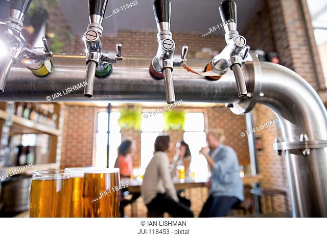 Close Up Of Bar Beer Pumps With Customers Drinking In Background