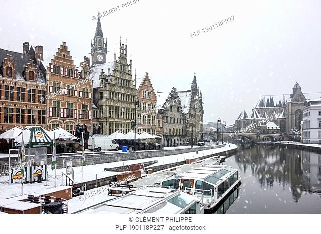 Tourist boats at the Graslei along the river Lys / Leie in the snow in winter in the city Ghent, East Flanders, Belgium