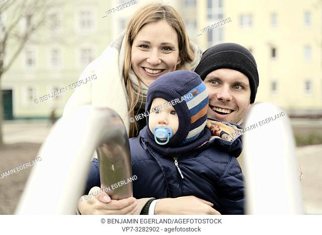 happy smiling parents with baby toddler child at playground outdoors, wearing winter clothes, in Cottbus, Brandenburg, Germany