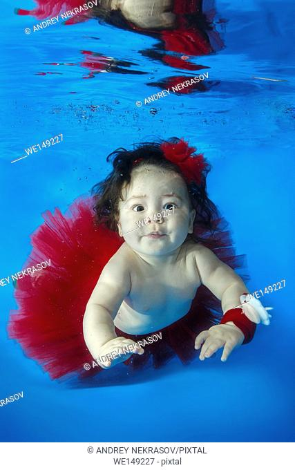 small girl in red skirt swim underwater in the pool