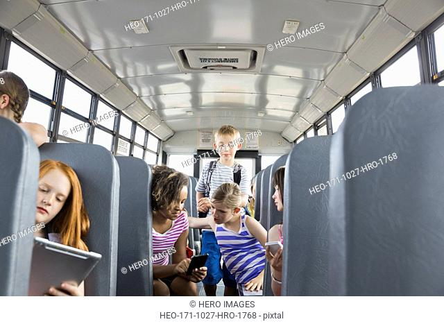 Schoolboy looking at girls using mobile phone across aisle of bus