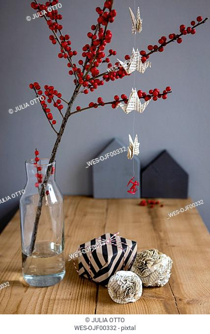 Wrapped present, paper decoration and twig of holly in vase