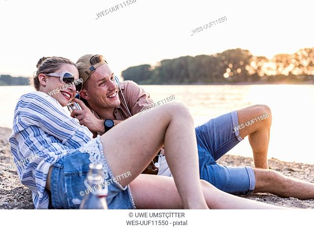 Young couple relaxing at the riverbank sharing headphones