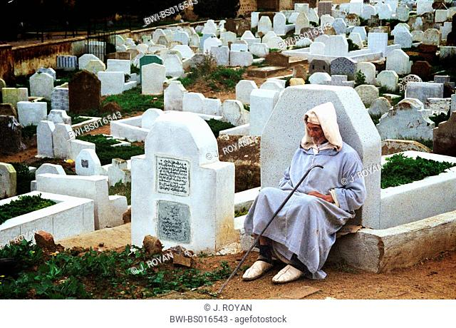 old man sitting allone behind a gravestone on a cemetery, Morocco, Fez