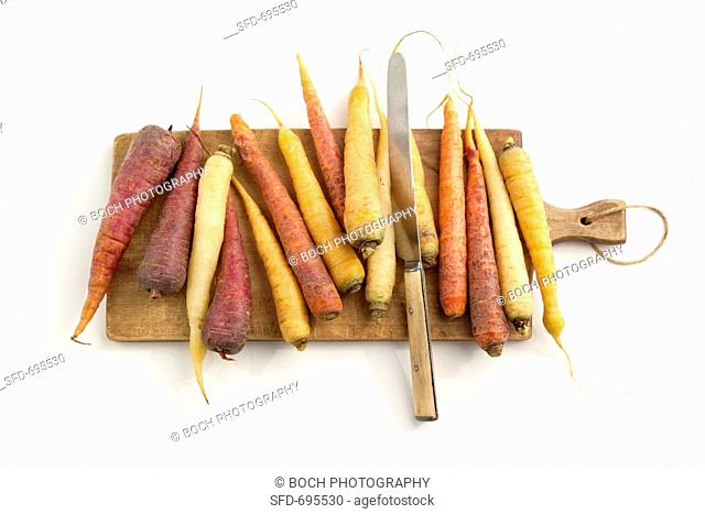 Heirloom Carrots on a Cutting Board with a Knife