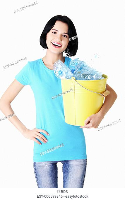 Attractive woman holding bin with plastic bottles. Recycling. isolated on white