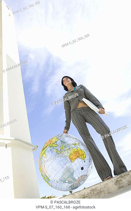 Low angle view of a businesswoman holding a laptop and a transparent globe