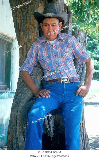 A Mexican-American cowboy leaning against a tree, AZ