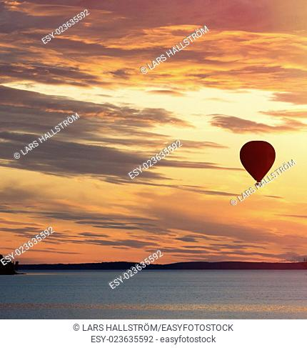 Hot air balloon flying over lake at sunset in beautiful and romantic landscape