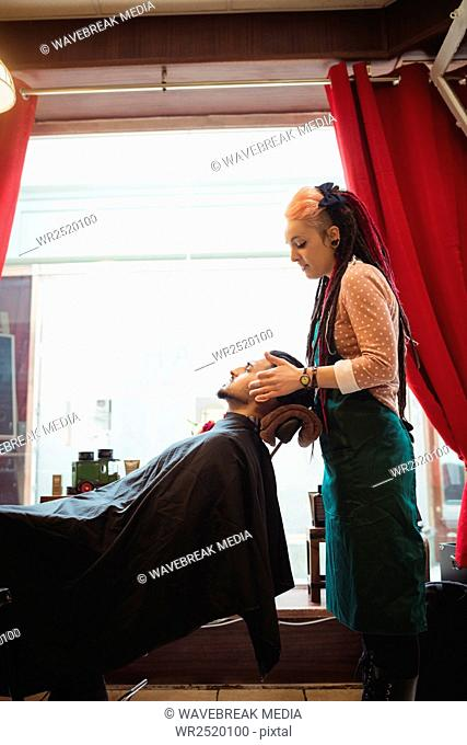 Man receiving a face massage from female barber