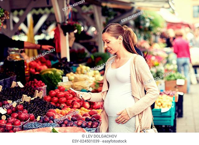 sale, shopping, food, pregnancy and people concept - happy pregnant woman with smartphone at street market