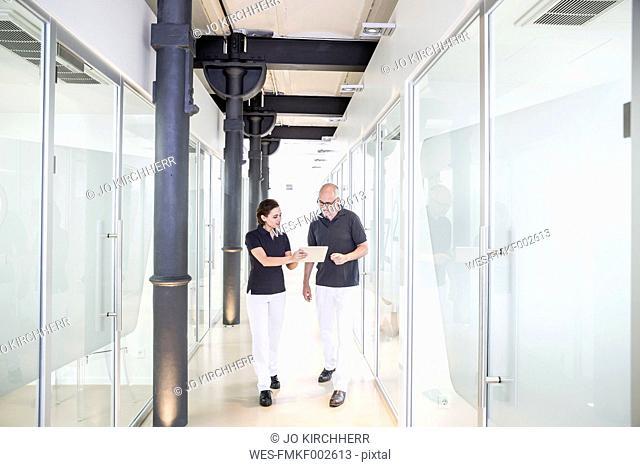 Two dentists using digital tablet in corridor