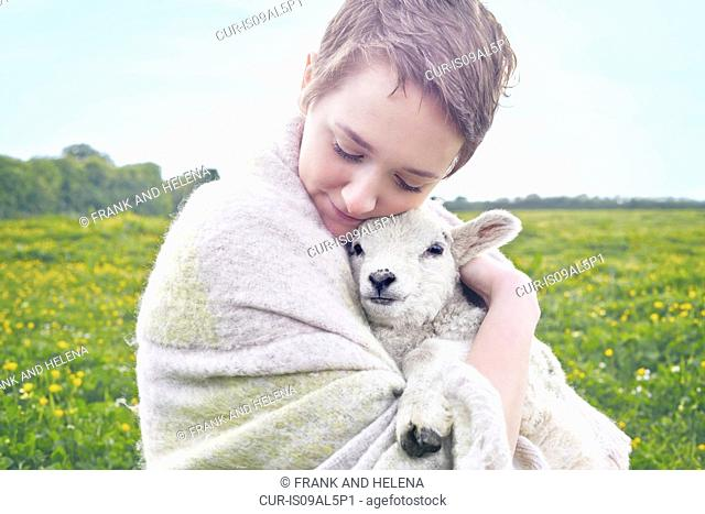 Portrait of young woman in field carrying lamb and wrapped in blanket